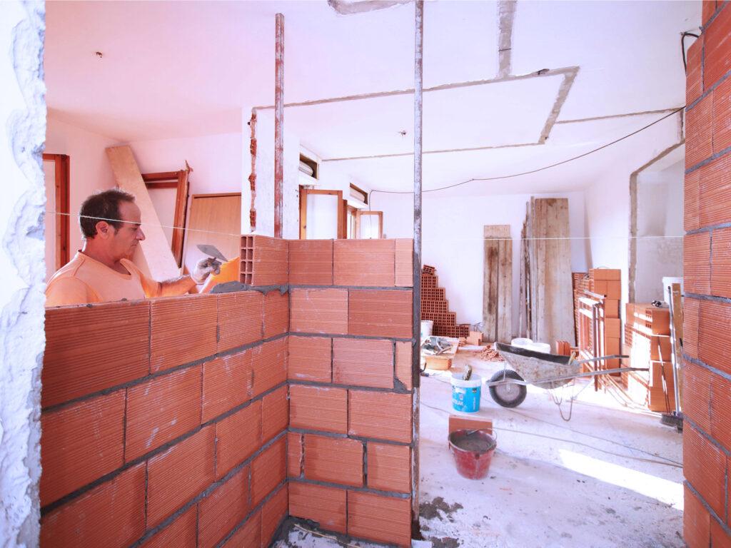 Muratore che costruisce un muro